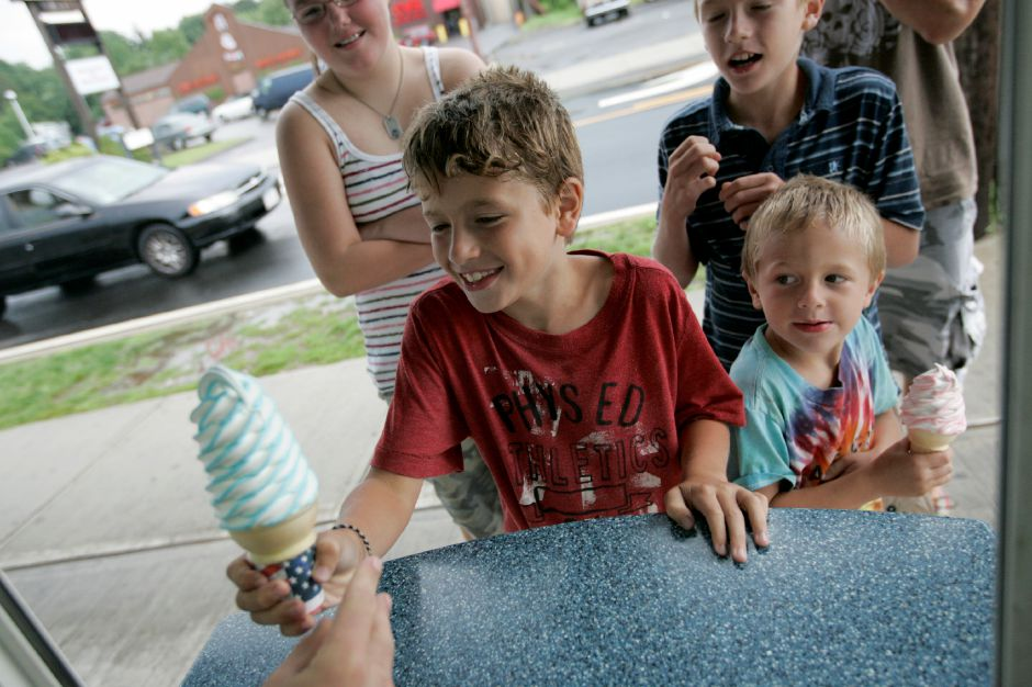 Record Journal Photo/ Johnathon Henninger 8.14.08 - Cameron Silver, 8, of Newington, reaches out for his ice cream while his little brother, left, Cooper Silver, 5, looks on. Eric Silver took his children as well as his fiance, Leanne Depre of Southington and her cousin, Jordyn McNamara to Les