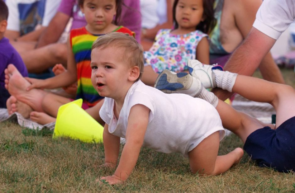 Patrick Morrison, 14-months-old, tries to crawl onto the field during the Frisbee Dog competition Wed., july 28 1999 at Doolittle Park as his dad, John orriso holds onto his ankle.