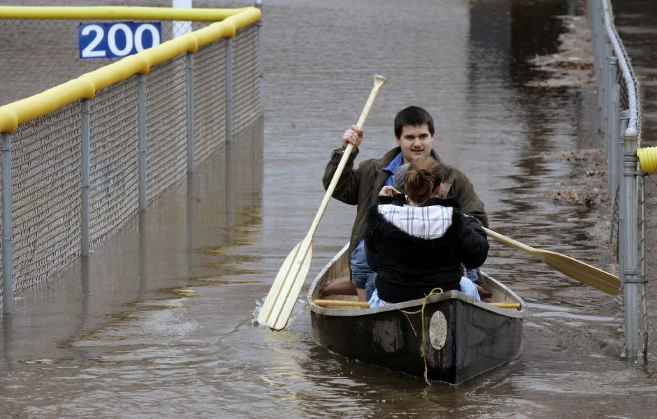 Steven Mendez, 16, of Meriden maneuvers his canoe between flooded fields at Habershon Park in Meriden Monday afternoon April 16, 2007. In the canoe are sisters Nicole, 11, and Katelyn, 8,. The Quinnipiac River borders the area and is flooding from heavy rain through the region. (dave zajac photo)