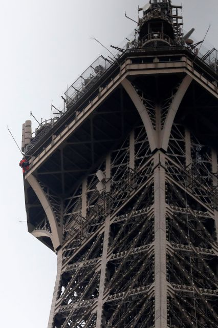 A rescue worker, left in red, climbs the Eiffel Tower Monday, May 20, 2019 in Paris. The Eiffel Tower has been closed to visitors after a person has tried to scale it. (AP Photo/Michel Euler)
