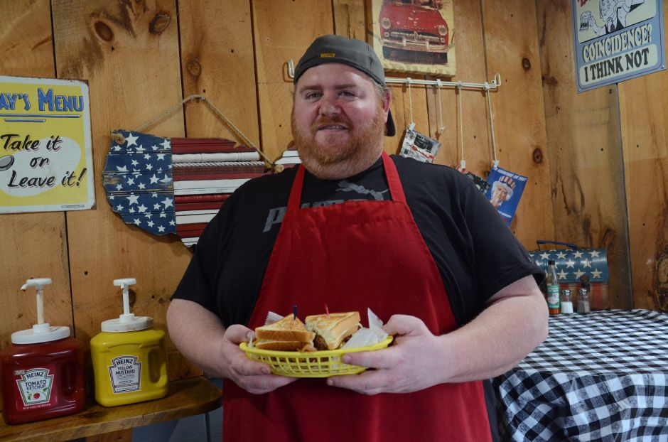 2 Guys One Grill owner Michael Wambolt holding the CheeSin Squeezin Burger.