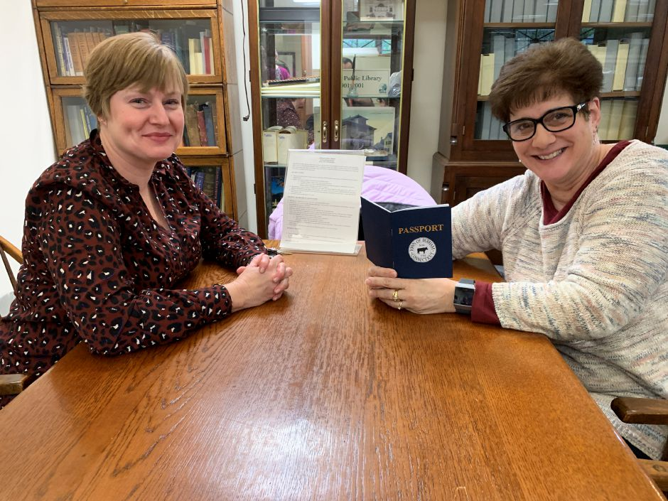 Assistant Library Director Kim McNally, left, sits with Durham EDC Chair Janet Morganti as they take a look at the Small Business Saturday passport.Photo by Everett Bishop, Town Times