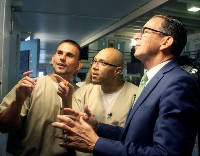 Inmates Festim Shyuqeriu, left, and Isschar Howard show Gov. Dannel P. Malloy around a unit of the Cheshire Correctional Institution in Cheshire in May. File photo, Associated Press