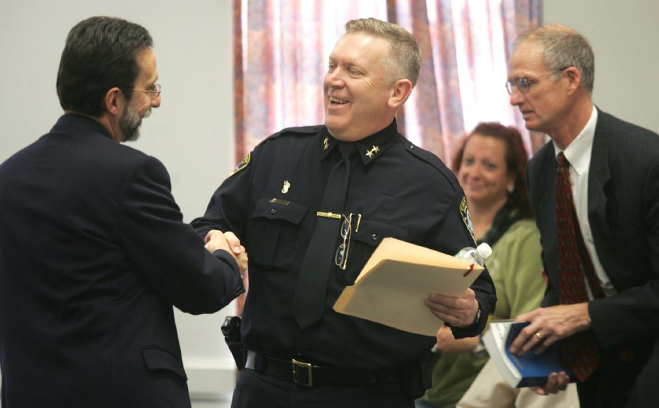 Cheshire Town Manager Michael Milone, left, shakes hands with Chief Michael Cruess, center, just before Cruess gets sworn in as the new chief of police during a ceremony at the Cheshire Town Hall Wednesday afternoon April 12, 2006. On the right is Ray Voelker the probate judge. Chris Angileri/Record-Journal.