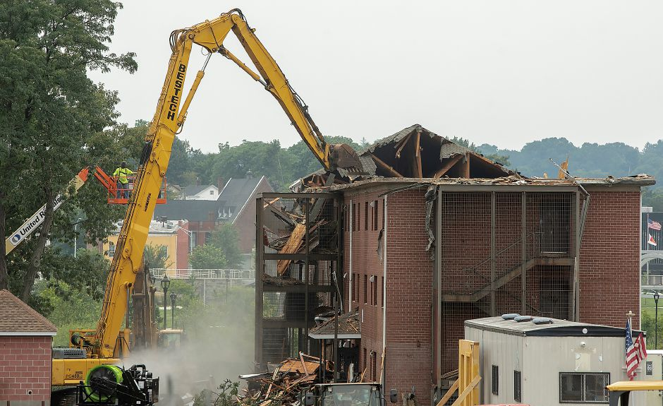 Demolition crews take down a building in the former Mills Memorial Apartments complex in downtown Meriden Friday. Dave Zajac, Record-Journal