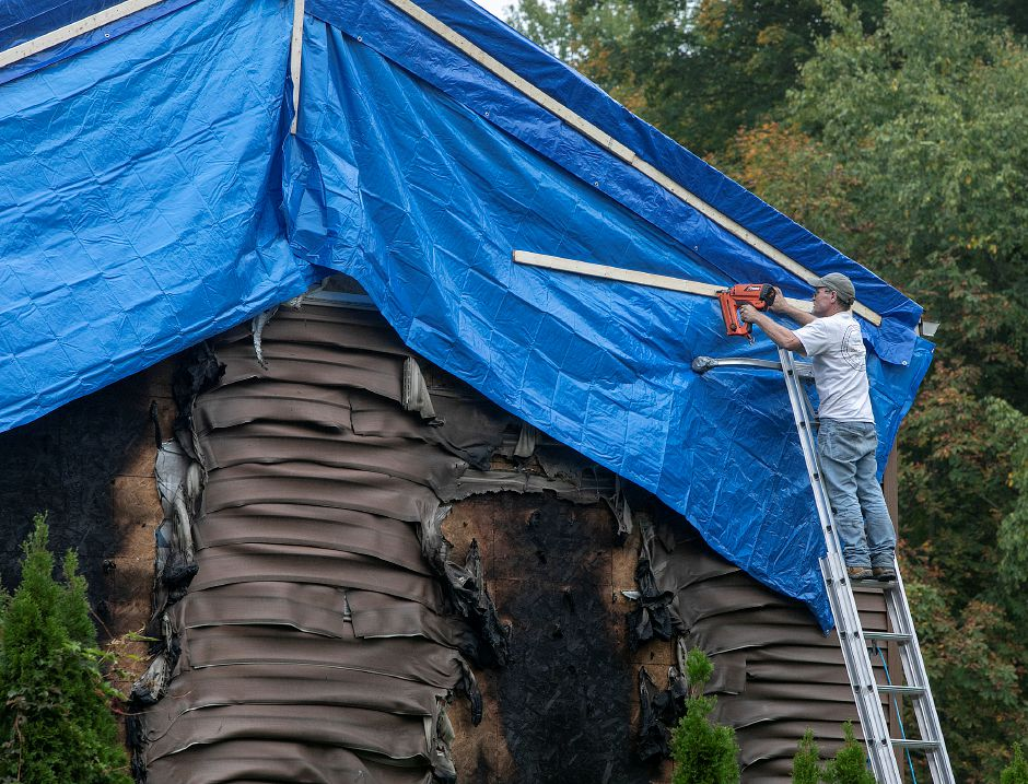A worker from United Cleaning and Restoration nails a cover in place after a fire damaged a home at 427 N. Elm St. in Wallingford, Monday, Oct. 8, 2018. Emergency crews responded to the blaze around 3:50 p.m. Sunday, which appears to have started in the garage. Dave Zajac, Record-Journal