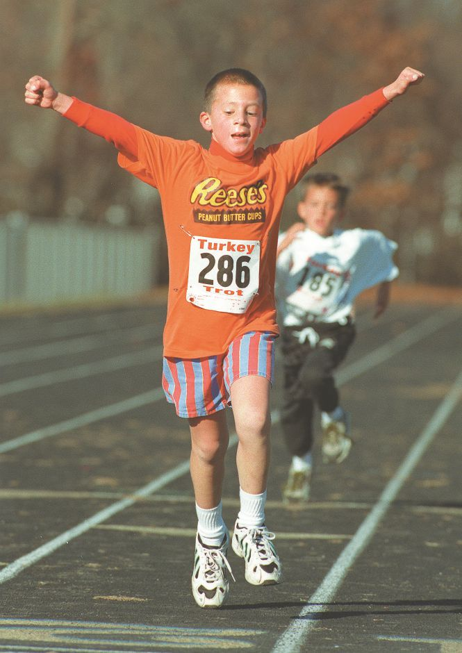 RJ file photo - Tony Cramond, 8, of Monroe, raises his arms on his way to second-place finish in the 1-mile fun run, which followed the start of the Turkey Trot at Lyman Hall High School in Wallingford Nov. 22, 1998.