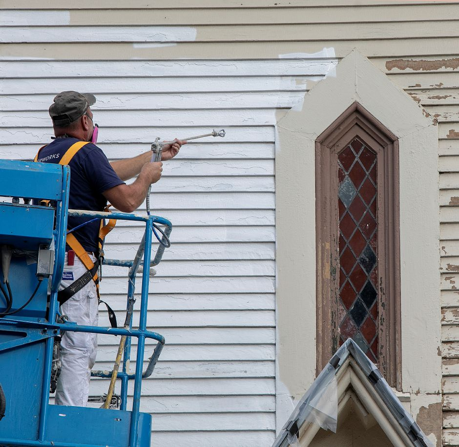 Dave Dixon, owner of Northeast Painting and Decorating sprays primer on the west side of Plantsville Congregational Church as renovations continue on the 1866 church, Tuesday, Oct. 9, 2018. Dave Zajac, Record-Journal