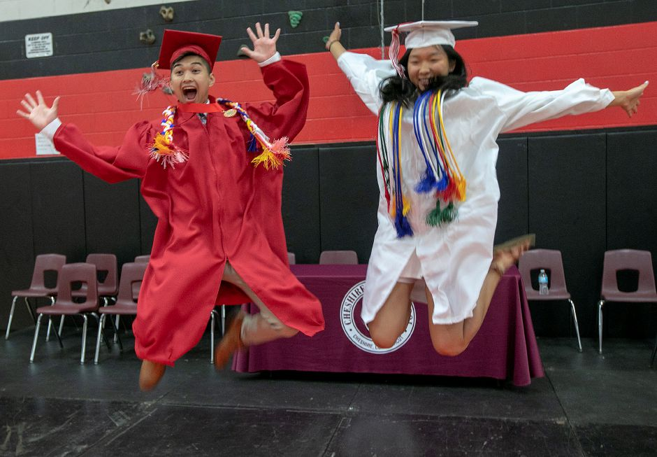 Graduates Richmond Le, 17, and Sydney Wang, 17, leap from a stage for a photo op prior to graduation ceremonies at Cheshire High School, Thurs., June 13, 2019. Dave Zajac, Record-Journal