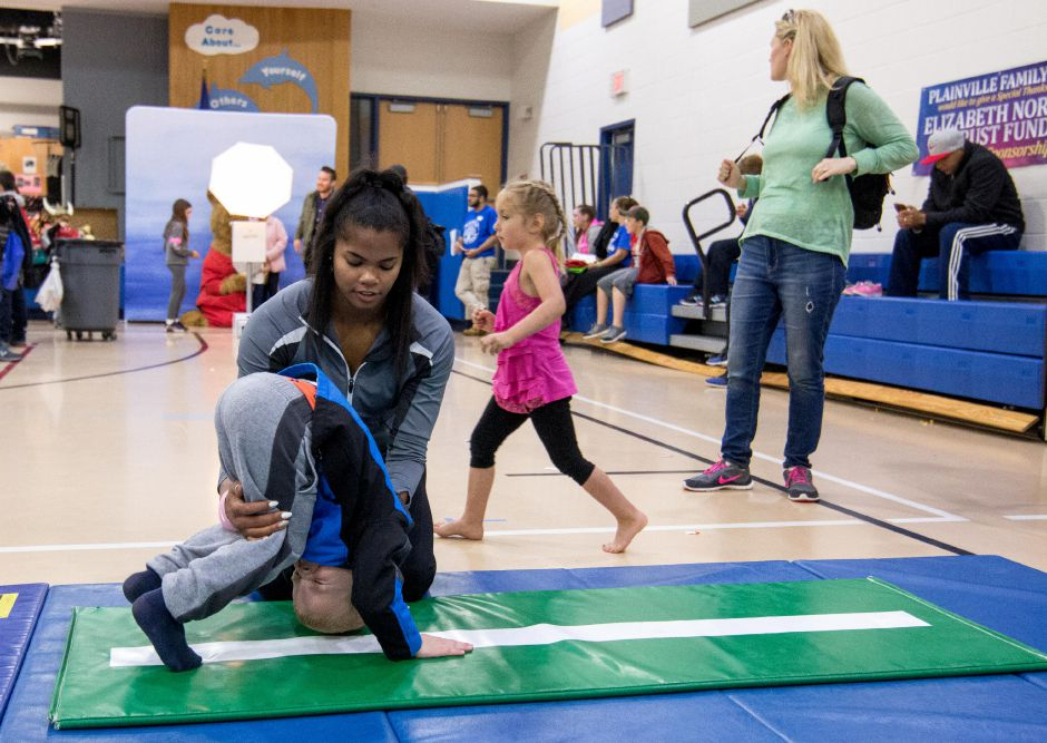 Sydni Spencer, of Farmington Valley Gymnastics, guides children through rolls at the Plainville Family Fest on Saturday, May 20, 2018. The event featured facepainting, a large set of model trains and dozens of vendors and organizations with tables throughout the halls of Linden Street School. | Devin Leith-Yessian/Plainville Citizen