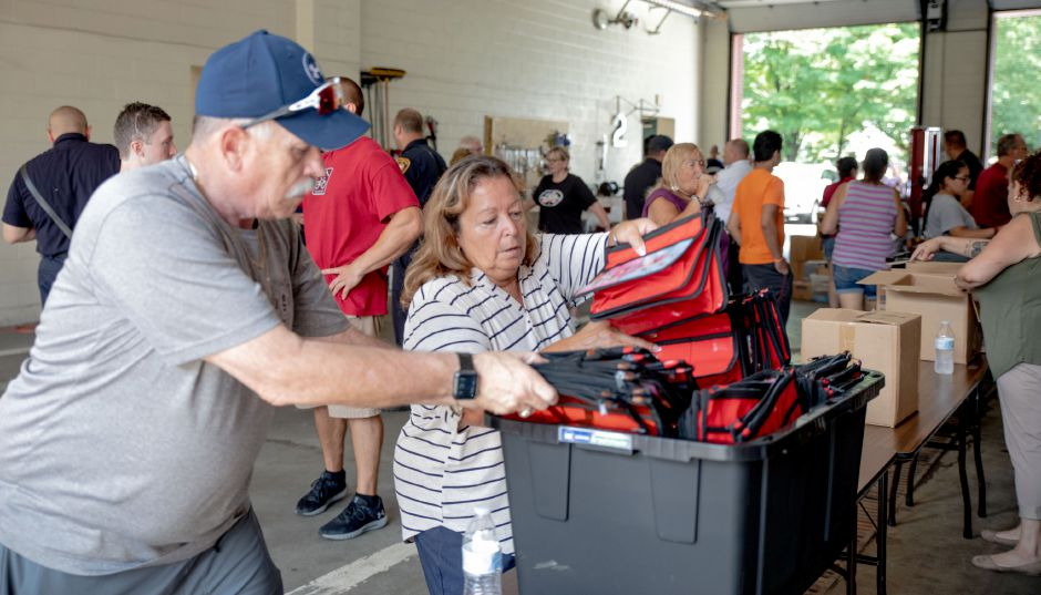 Sandy Conway, of Meriden, right, is helped by Meriden Fire Chief Ken Morgan as she packs up pencil pounches left over after volunteers filled hundreds of backpacks with school supplies at Station One on August 18, 2019. Every summer, city firefighters fill backpacks for the Meriden Back to School Expo, where students can get free backpacks and school supplies. | Devin Leith-Yessian/Record-Journal