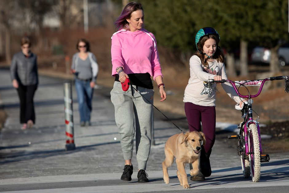 Jessica Majewicz, daughter, Kaylee Miglietta, 8, and dog, Cooper, of Southington, walk the Farmington Canal Heritage Trail during a warm winter afternoon in Southington, Mon., Feb. 4, 2019. Dave Zajac, Record-Journal