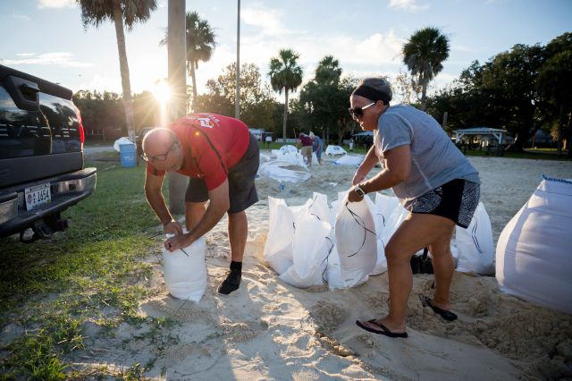 Filling sandbags with sand provided by the City of Tybee Island, Sib McLellan, left, and his wife, Lisa McLellan, prepare for Hurricane Florence, Wednesday, Sept., 12, 2018 on Tybee Island, Ga. (AP Photo/Stephen B. Morton)