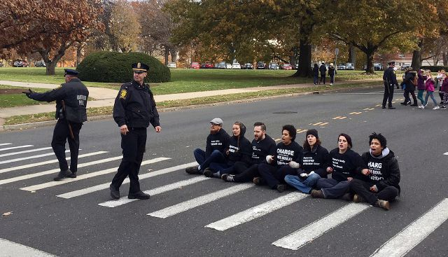 People sit in a street outside the state Capitol on Monday, Nov. 27, 2017, in Hartford, Conn., to demonstrate the handling of the case of Jayson Negron, 15, killed by police in May in Bridgeport. The seven protesters were arrested. Community advocates had called for a rally to bring attention to Negron