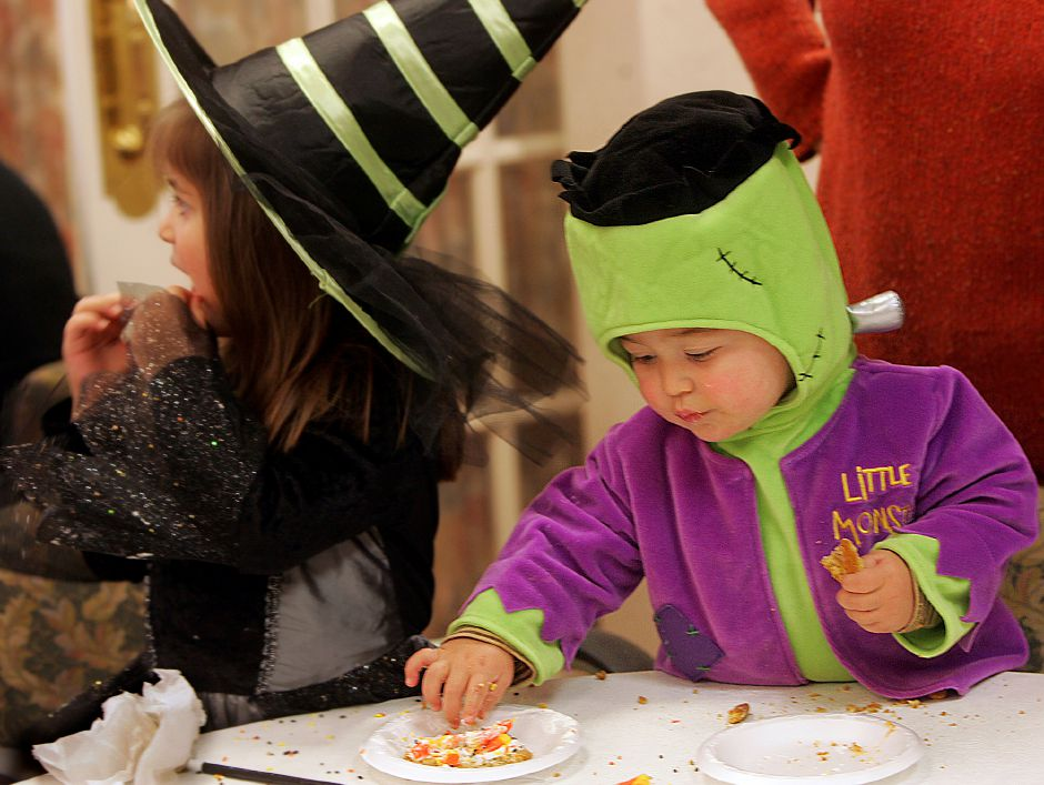 Jacob Rivera, 1, of Cheshire wears a Frankenstein costume while helping himself to sister Emily