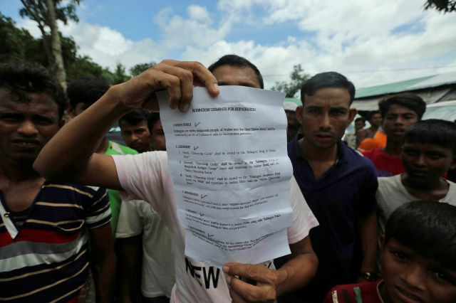 A Rohingya refugee displays to journalists a demand letter about Rohingya repatriation at Nayapara camp in Cox