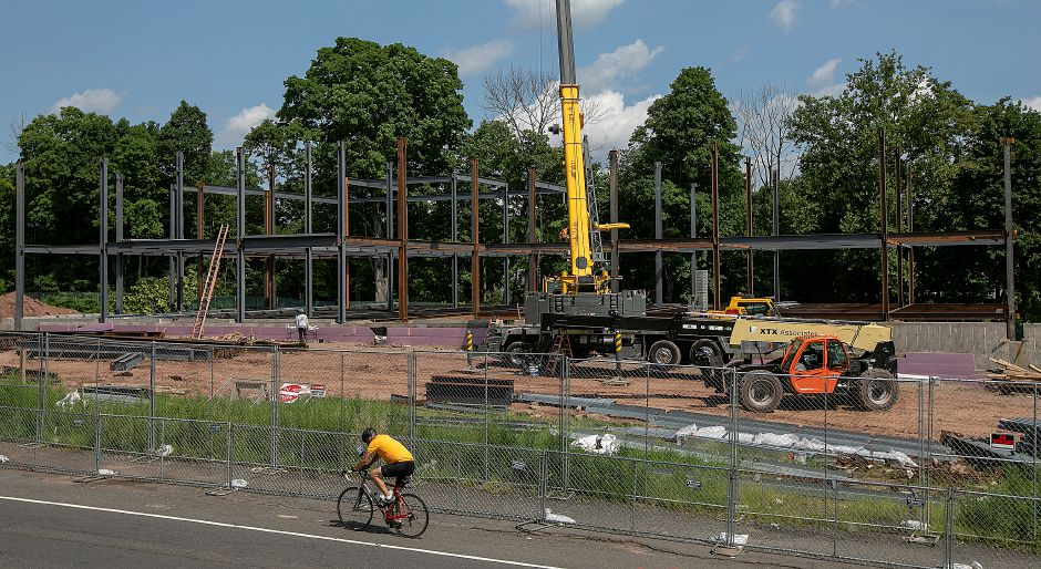 A cyclist pedals by the Hartford HealthCare medical facility under construction on South Main Street in Cheshire, Wednesday, August 15, 2018. Dave Zajac, Record-Journal