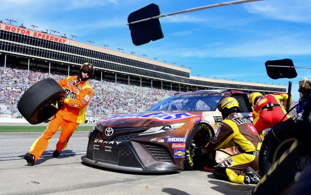 Crew members tend to Kyle Busch