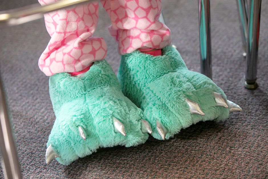 Student Laura Pressley, 12, wears dinosaur slippers with her pajamas while in her seventh-grade class during PJ Day for the Kids at Our Lady of Mount Carmel Elementary School in Meriden, Fri., Dec. 14, 2018. Students and staff participated in PJ Day for the Kids in support of patients at Connecticut Children's Medical Center. The one dollar donation per person is to honor children at the hospital who wear their PJs for days, weeks or longer while fighting cancer or other serious illnesses. Dave Zajac, Record-Journal