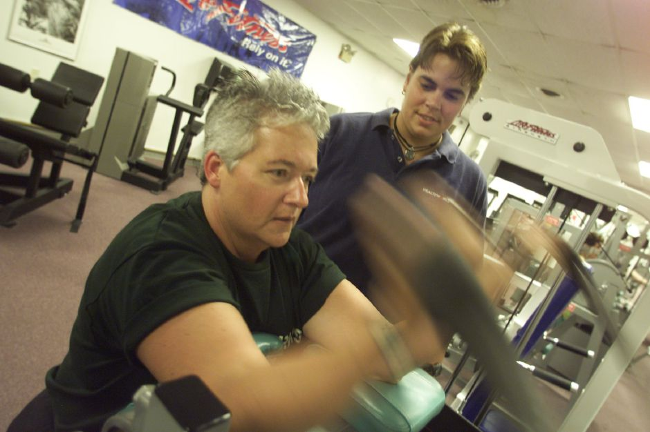 Lynn Faria, left, an interum Executive Director of Healthworks in Wallingford, works out with Denise Allen, of Wallingford, a Fitness Director at Healthworks July 23, 1999. Allen works out with Faria as her personal fitness instructor five days per week. Faria is working out her biceps on a machine. BIZ story