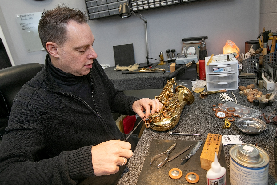 Jonathan Ball, owner of The Music Lab, LLC, works to repair an alto saxophone.