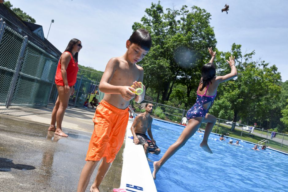 Eight-year-old Noah Soto, center, puts on goggles while his sister Amaliah, 9, jumps for a toy her father Alex threw at the Hubbard Park Pool in Meriden on Friday, July 19, 2019. | Bailey Wright, Record-Journal