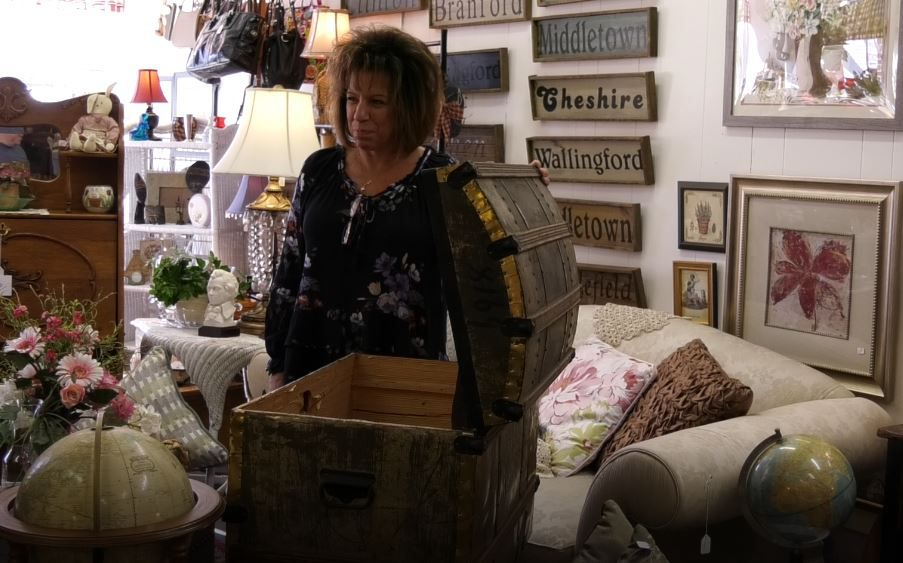 Owner Cindy Ruszczyk shows customers a trunk for sale at Cindy