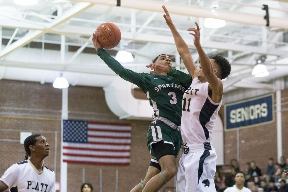 Maloney's Vincent Martinez puts in a layup as Platt's Roemello Leary defends. Martinez led the Spartans with 25 points.
