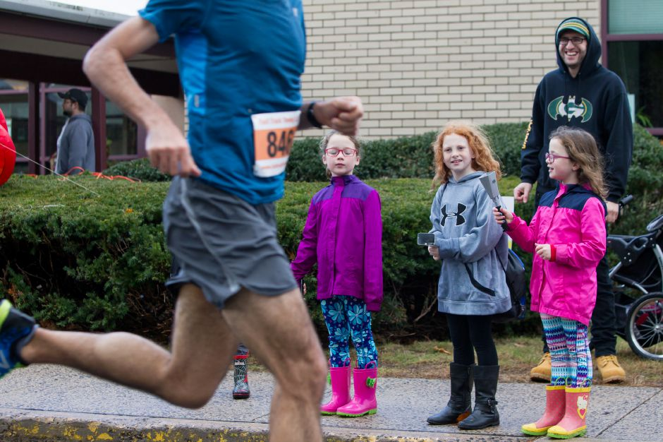 Delaney Frank 8 left Harper Vanacore 8 and Briley Frank 8 all of Wallingford ring their cow bells as runners come in Sunday during the Kiwanis Club 5 mile and 5K Turkey Trot Road Race at Stevens Elementary School in Wallingford November 19, 2017 | Justin Weekes / For the Record-Journal