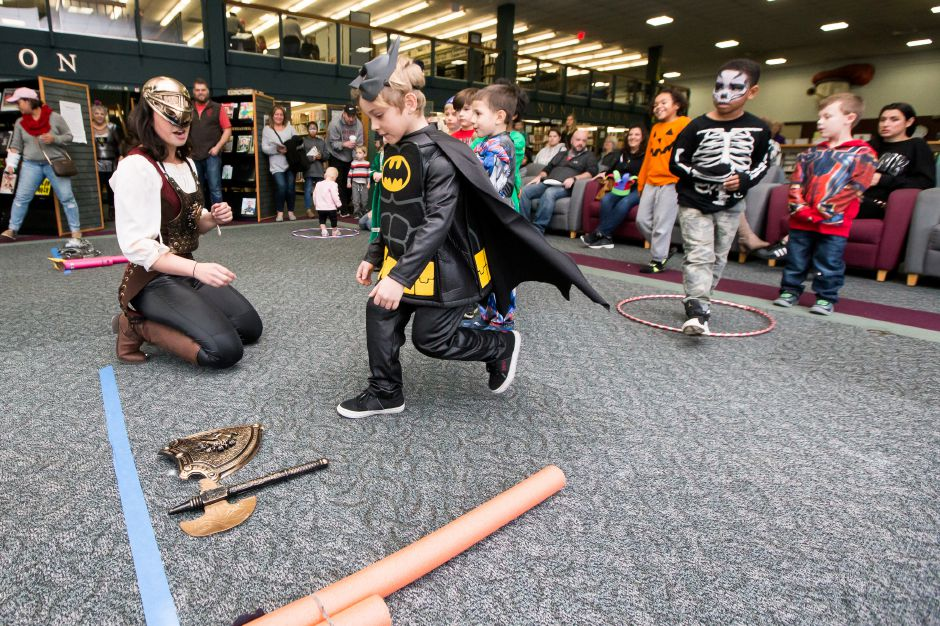 Molly Virello show Noel Telha 6 of Southington how to put on the Knight armor Saturday during the 2nd Annual Renaissance Fair at the Southington Library in Southington November 10, 2018 | Justin Weekes / Special to the Record-Journal