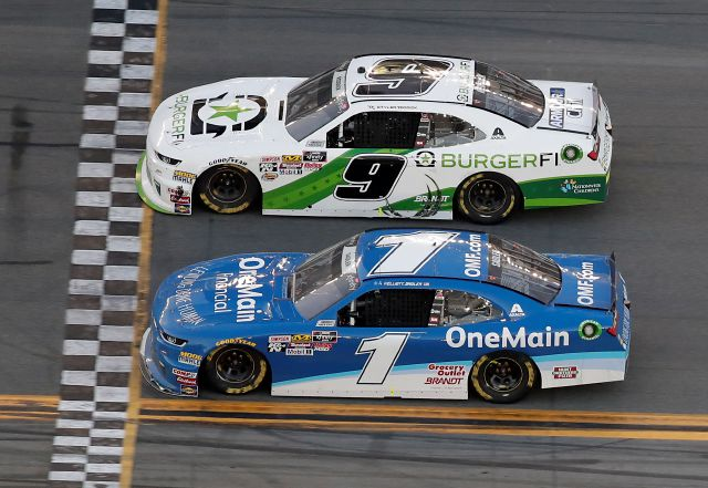 Tyler Reddick (9) crosses the finish line ahead of Elliott Sadler (1) to win the NASCAR Xfinity Series auto race at Daytona International Speedway, Saturday, Feb. 17, 2018, in Daytona Beach, Fla. (AP Photo/John Raoux)