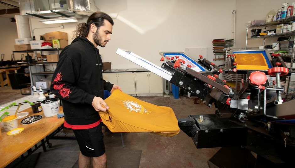 Giovanni Richetelli, production manager, operates a screen press while making custom designed T-shirts at Micro Print Shop