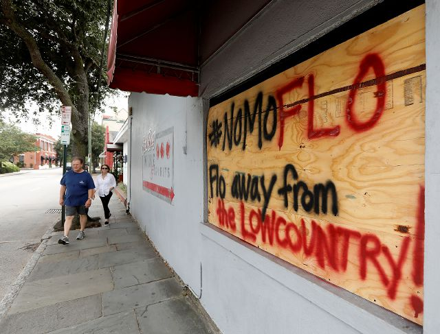 Michael and Polly Long walk down East Bay St. past a sign asking for Hurricane Florence to spare the Lowcountry in Charleston, S.C., as Hurricane Florence spins out in the Atlantic ocean Thursday, Sept. 13, 2018. (AP Photo/Mic Smith)