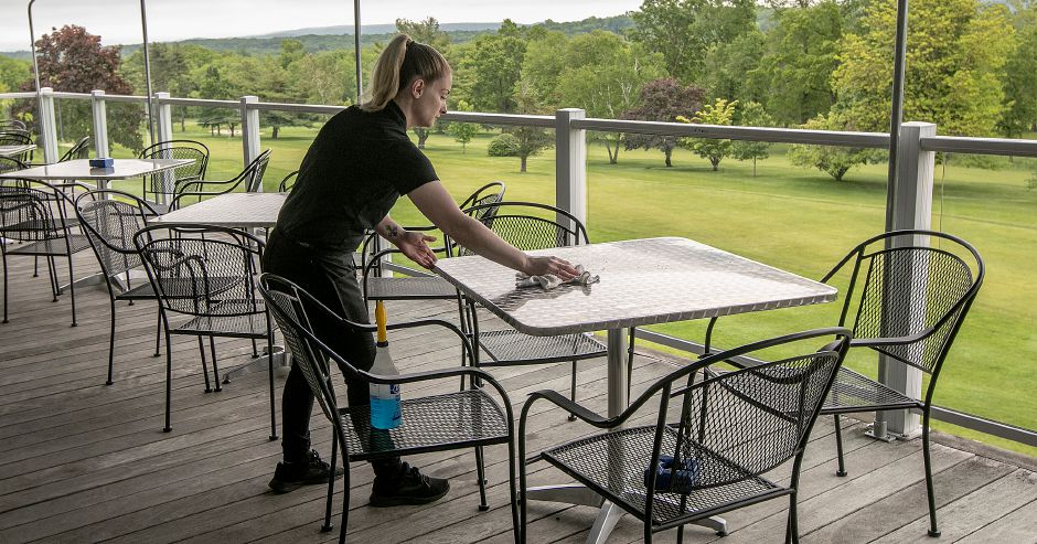 Server Julie Giannetta, of Wallingford, prepares outdoor dining tables.