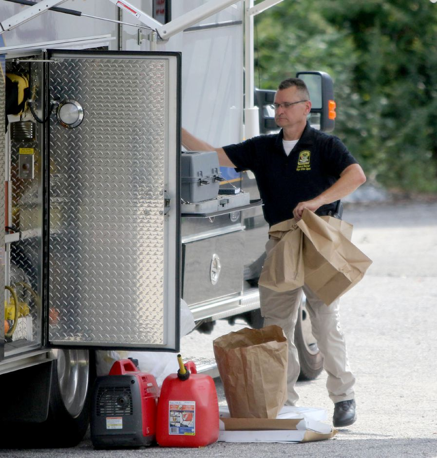 An investagator for the Connecticut State Police Major Crime squad carries eviednce from ther far side of the warehouse at 137 Brookside Road in Waterbury Thursday August 21, 2109. Police found human remains at the site which may be connected to the dissapearance of Perrie Masson 31, a missing person from Meriden. Aaron Flaum, Record-Journal