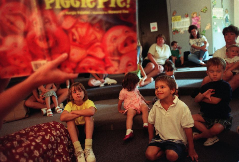 "Colby Cortella, 4, from Wallingford and Kathleen Adams, age 7, also from Wallingford listen to the ""Piggie Pie"" story at the Wallingford Library Thursday morning July 22, 1999."