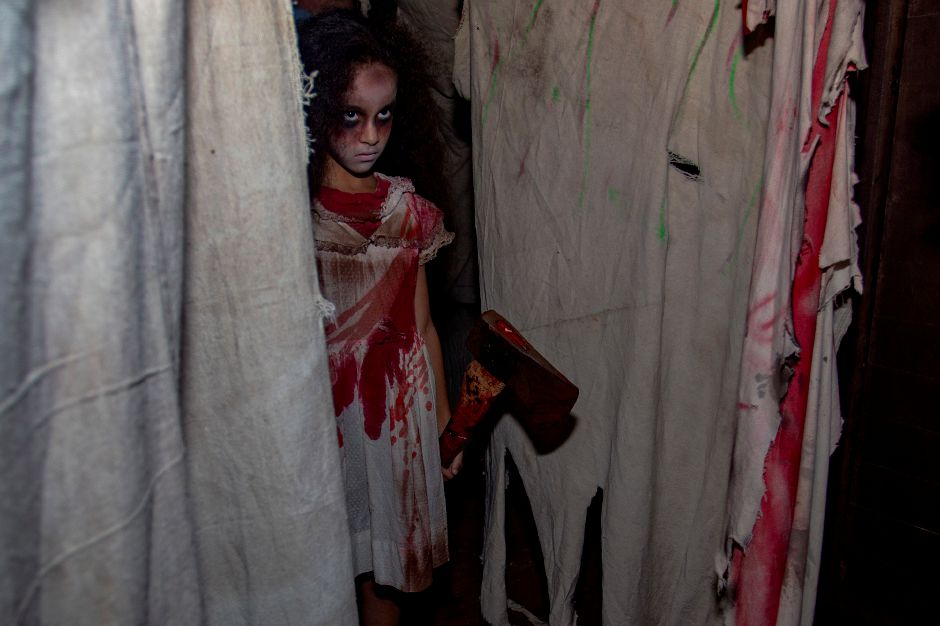 Amelia Donis, 8, peers out from behind a curtain at the Haunt on Eden in Southington Oct. 3, 2018. | Richie Rathsack, Record-Journal