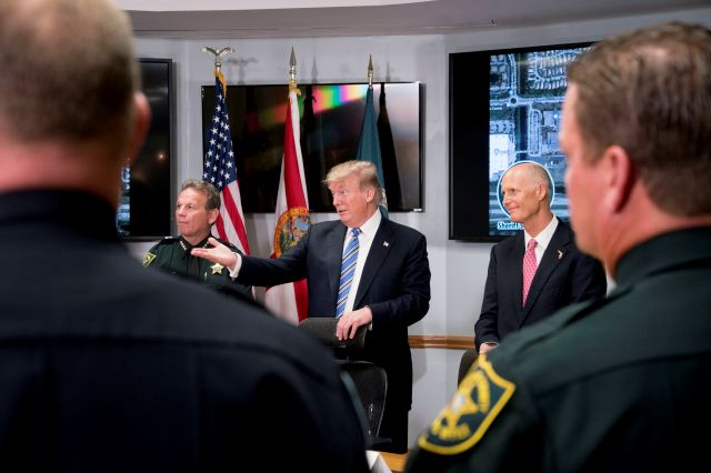 In this Feb. 16, 2018, photo, President Donald Trump, center, accompanied by Broward County Sheriff Scott Israel, left, and Florida Gov. Rick Scott, right, speaks as they meet with law enforcement officers at Broward County Sheriff