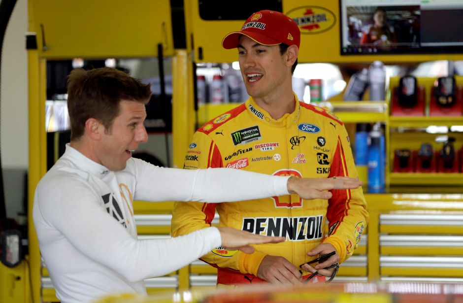 Joey Logano, right, listens to Jamie McMurray before practice for the Daytona 500 auto race, Friday, Feb. 15, 2019, at Daytona International Speedway in Daytona Beach, Fla. (AP Photo/Chris O