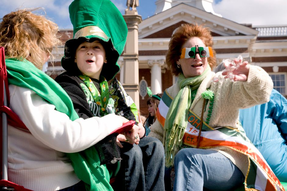 From left: Cindy Dadostino, Bobby Nadwairski and Lisa Fornaciari smile and throw candy from aboard a flatbed truck carrying members of the L.A.O.H. from Meriden during the St. Patrick
