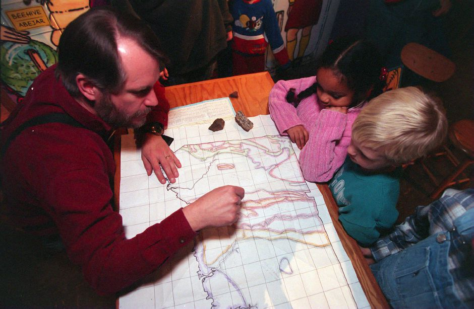 RJ file photo - Southington resident John Hunter, a volunteer at the Science Center of Connecticut, shows Kasia Plessy, left, and Alex Sedergren, both six, what kinf of rock can be found where they live, March 1999.