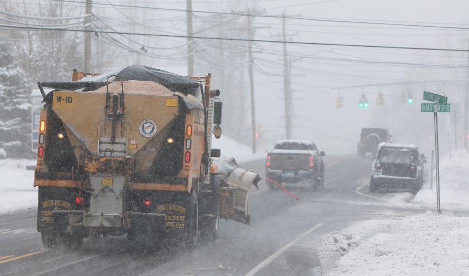 A city plow heads west on East Main Street in Meriden during Tuesday