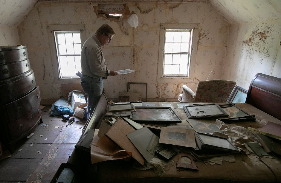 Local developer John Ricci looks over items left behind from a previous tenant in the Nathaniel Ives house at 257 Fenn Rd. in Cheshire, Monday, Oct. 8, 2018. Ricci is owner of the house built around 1749 and is considering how to develop the 50-acre property. Dave Zajac, Record-Journal