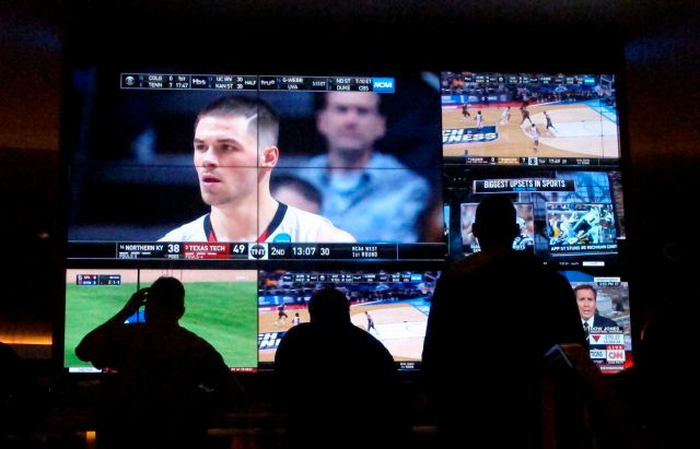 In this March 22, 2019 photo, customers watch a game during the NCAA March Madness college basketball tournament at the Hard Rock casino in Atlantic City N.J. Casinos in eight states are opening or expanding retail sportsbooks to capture in-person sports betting business, even while most of the growth in the new industry is forecast to be online. (AP Photo/Wayne Parry)