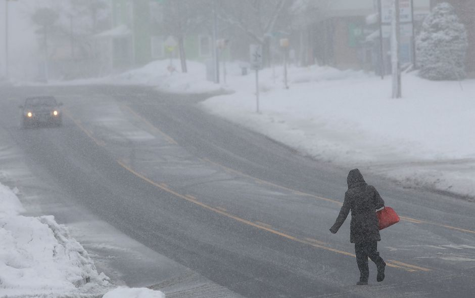 A woman crosses East Main Street at Murray Street in Meriden during Tuesday