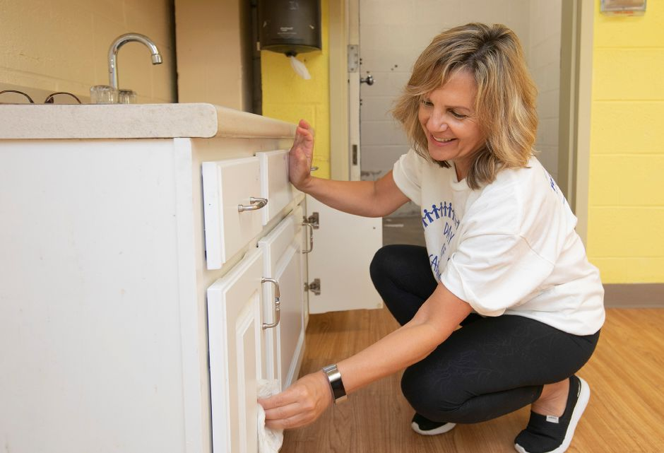 Diana Minelli, director of human resources at The Marlin Company, cleans up a cabinet while volunteering during the United Way