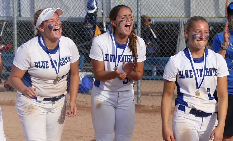 Abby Lamson, left, and Gabby Verderame-Malachowski, middle, cheer for fellow senior Chrissy Marotto after the shortstop was named Most Valuable Player of the Class LL state softball championship game Saturday at DeLuca Field. The Blue Knights beat NFA 7-6 to claim Southington's 18th state title. It was Southington's first crown since 2015 and the first for this year's senior class, which desparately wanted to extend the program's legacy. | Spencer Davis, Record Journal