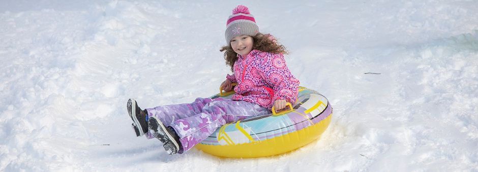 Eliza Emfinger, 7, of Southington, takes a tube ride down the hill.