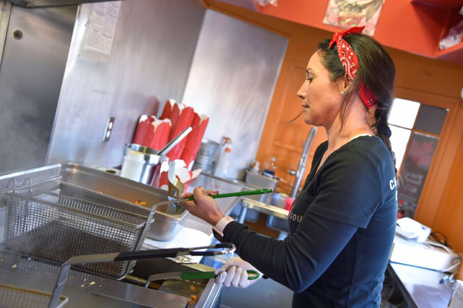 Lisa Greene, Poutine Gourmet food truck partner, puts together french fries, cheese curds, gravy, and toppings for customers at the Apple Harvest Festival in Southington on Oct. 4, 2019. | Bailey Wright, Record-Journal
