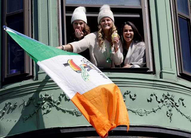 Spectators wave an Irish flag while watching the annual St. Patrick
